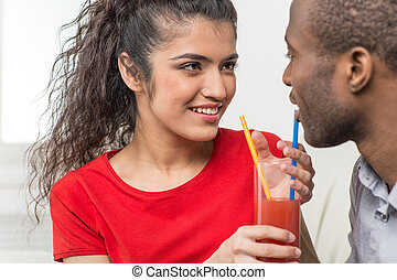 Young couple sharing glass of orange juice. black man and...