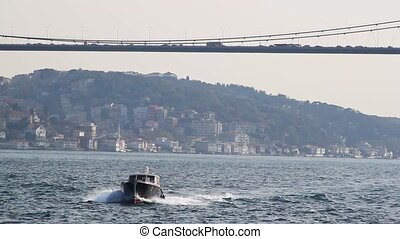 Boat on the Bosphorus under bridge