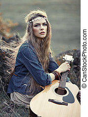 Beautiful hippie girl with guitar sitting on grass near...