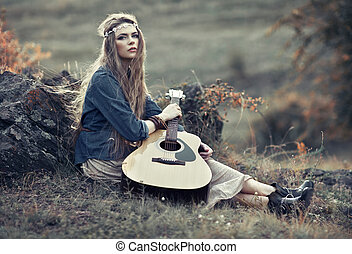 Beautiful hippie girl with guitar sitting on field near...
