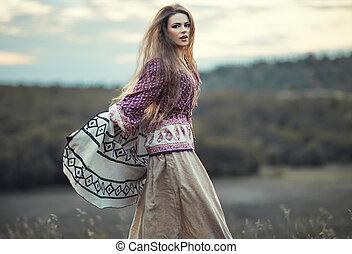 Beautiful hippie girl jumping outdoors at sunset Boho...