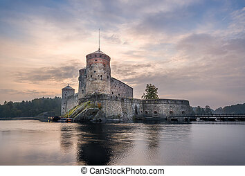 Olavinlinna fortress at sunrise. Early morning in...