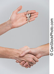 Two businessperson shaking hands on grey background only...