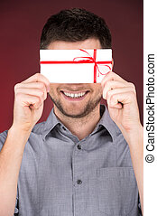 Present gift in hands of smiling man. closeup on happy man...