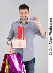 man holding bagsand boxes with credit debit card. young...