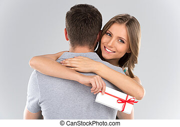 Young couple hugging with wrapped present woman embracing...