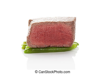 Beefsteak. Big sirloin steak on green beans isolated on...