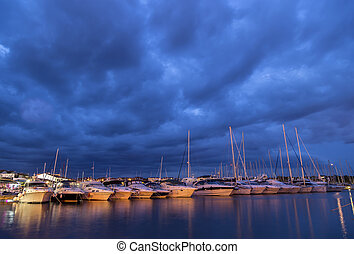 Yachts in a harbor evening - Yachts in a harbor in the...