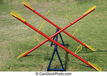 Yellow Red and Blue See Saw - A metal see saw in a childrens...