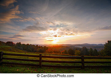 Sunrise meadow - The sun rises over the mountains with..