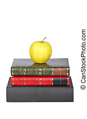 Yellow apple on old books