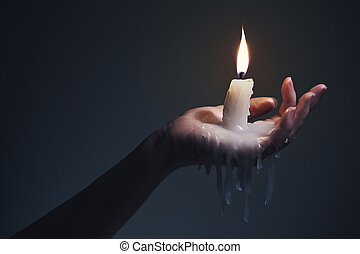 Holding a candle on a dark background - Holding a lit candle...