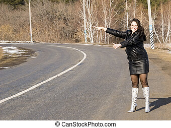 woman on road - woman hitching a ride on a road