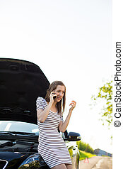Pretty, young woman calling the roadside serviceassistance...