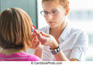 Optometry concept - pretty, young female optometrist...