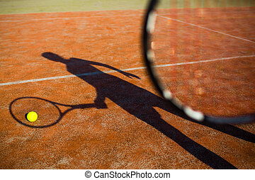 Shadow of a tennis player in action on a tennis court...