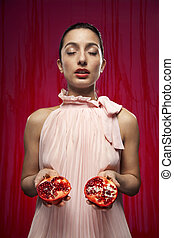 Pom Pom Grenades - A beautiful young woman holds up a slices...