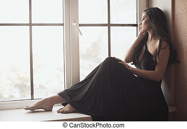 Beautiful young woman on the window