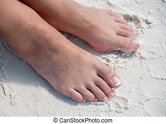 Relaxing at a beach, with beautiful woman feet in the warm sand