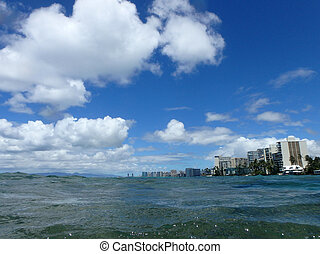 Ocean waters ripple off the coast of waikiki with hotels lining
