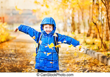 little boy throws the autumn leaves