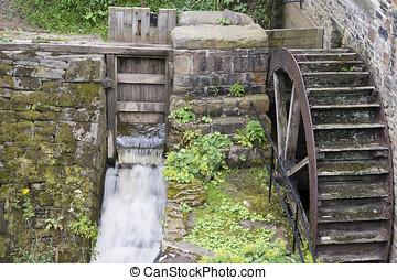 Waterwheel - Old wooden waterwheel on the side of a mill
