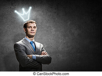 Business king - Young handsome businessman with crown above...