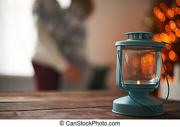 Lantern on wooden table on background of lovers