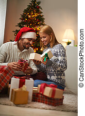 Christmas gifts - Cheerful couple opening giftboxes on...