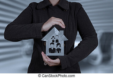 businessman hand holding 3d house with family icon as insurance