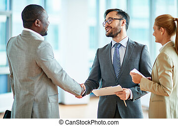 Happy partners - Two businessmen making agreement, their...