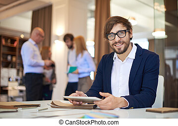 Happy employee - Modern businessman with touchpad looking at...