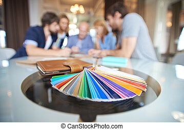 Color palette on workplace with group of business people on...