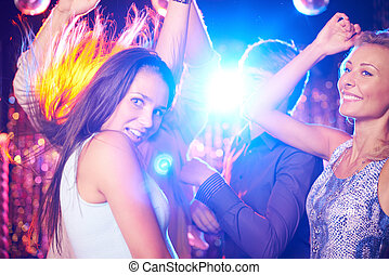 Clubbers on dance-floor - Energetic young people dancing in...