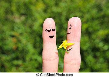 Finger art of a Happy couple. Man is giving flowers to a...