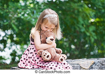 Child Kissing Teddy - Adorable little girl giving her teddy...