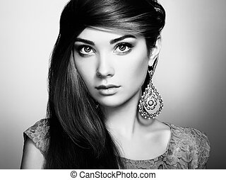 Portrait of beautiful young woman with earring. Jewelry and...