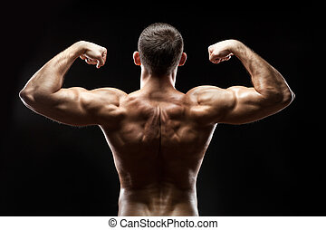 Man back shows big muscles - The man is standing back and...
