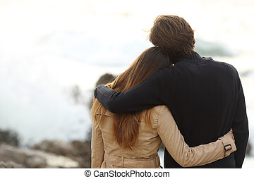 Back view of a couple cuddling in winter isolated in white...