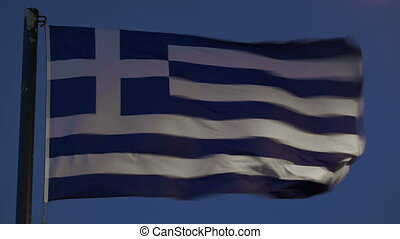 Greek flag fluttering against evening sky - Close-up shot of...