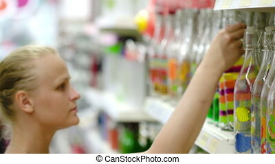 Woman looking at decorative bottle in the store
