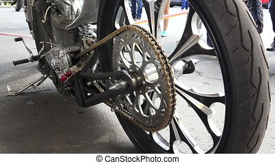 The asterisk at the rear wheel of the motorcycle.