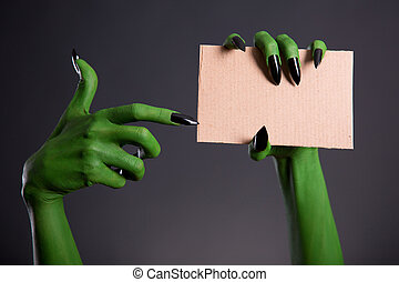 Green monster hand with black nails pointing on blank piece...