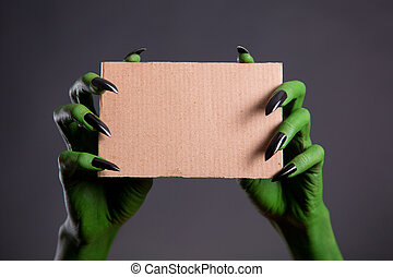Green hands with black nails holding empty piece of...