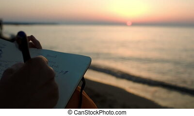 Woman making notes sitting by sea at sunset - Close-up shot...