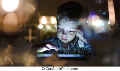 Boy playing on tablet computer in cafe