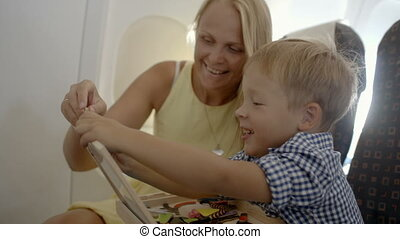 Mother and son playing game in the plane - Mother and son...