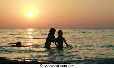 Girls playing with ball in sea at sunset - Three girls...