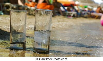 Pouring water into two glasses on beach