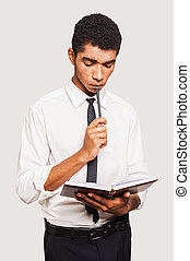 The next step will be... Thoughtful young Afro-American man in formalwear holding a note pad and touching his chin with pen while standing against grey background